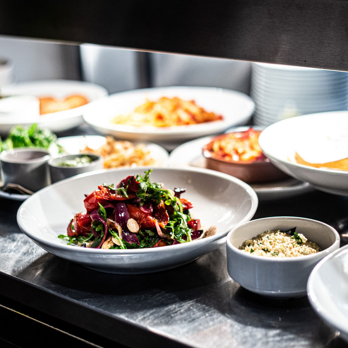 Photo of bowls of food in a kitchen, ready to be taken customers