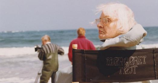 Woman sitting on chair on beach with filmmakers behind her.