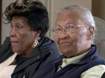 Two older black women, one looking into the camera