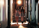 Twin girls stand at the end of an eerily lit corridor