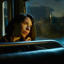 Photo of a woman wistfully looking out on a sunsetting sky from a bus window. From the film The Shape of Water.