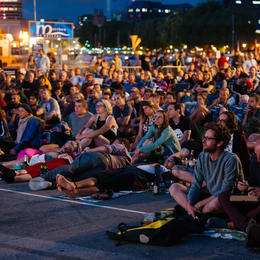 Photo of people sat on the ground watching g a cinema screening in Bristol harbourside