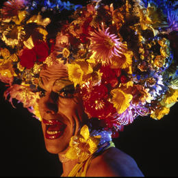 Person wearing a big floral wig and making a face