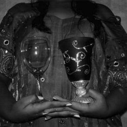 Photo of a young woman, holding two glasses