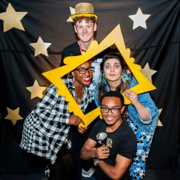 Photo of four young people, dressed up and celebrating