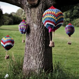Mini wool balloons hanging from a tree