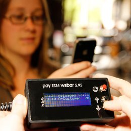 Woman using a phone to make a £B payment at Watershed Bar