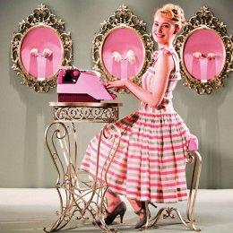 Woman dressed in pink sitting at typewriter smiling.