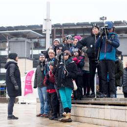 Group of people holding phones up with selfie sticks
