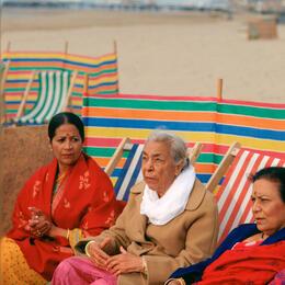 Three women sitting on deckchairs on the beach