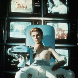 David Bowie sitting in a chair in front of TV screens