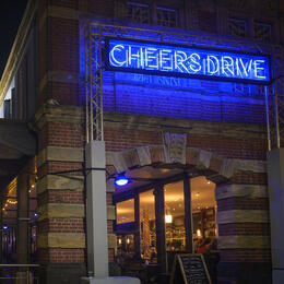 Photo of the exterior of Watershed at night with a large neon sign saying Cheers Drive, as part of Bristol Light Festival