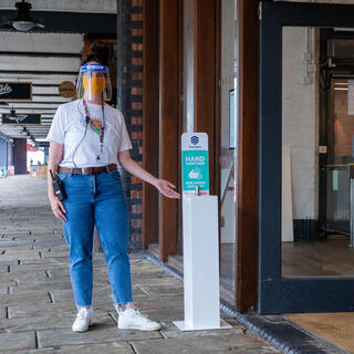 Photo of the entrance to Watershed with a woman welcoming customers and pointing at a hand sanitiser station at the entrance