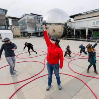 Photo of people wearing VR headsets in Bristol's Millenium Square taking part in Dancing Shadows
