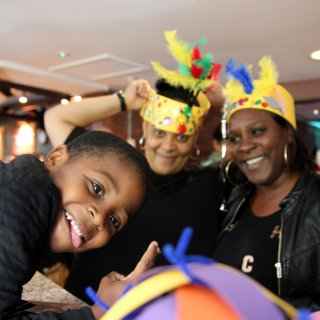 Photo of a child and two adults smiling to the camera at a paper hat making workshop at Watershed
