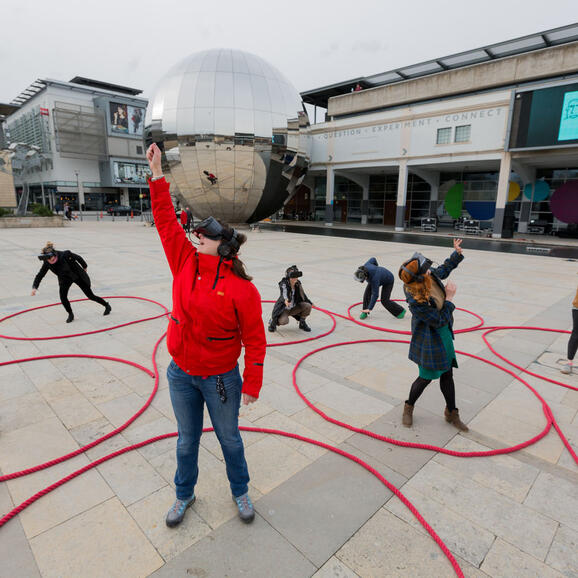 Photo of a group of people with VR masks on in Millennium Square, Bristol