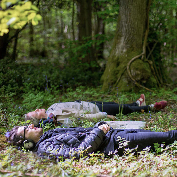 Still from Afterlife - two people lying in a wood listening to headphones