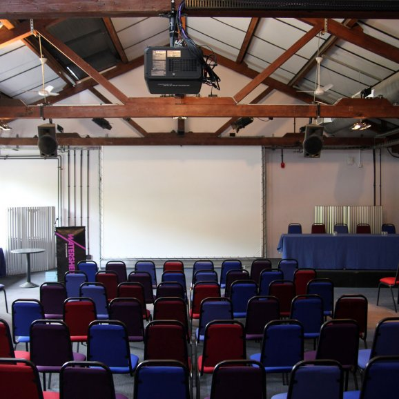Photo of Waterside 3 at Watershed –a large room with chairs facing a projector screen, a speakers podium and top table