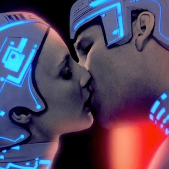 Scene from Ton - a  couple dressed in neon headgear kissing.