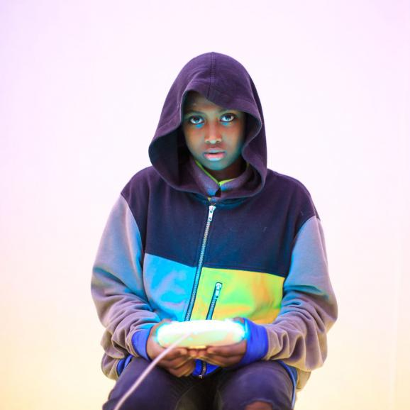 Girl in a hood sitting down holding a glowing light