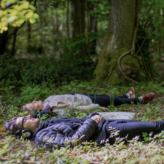 Two people lying down in the woods with headphones on