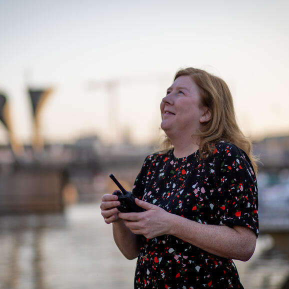 Woman holding a walkie talkie looking up at the sky