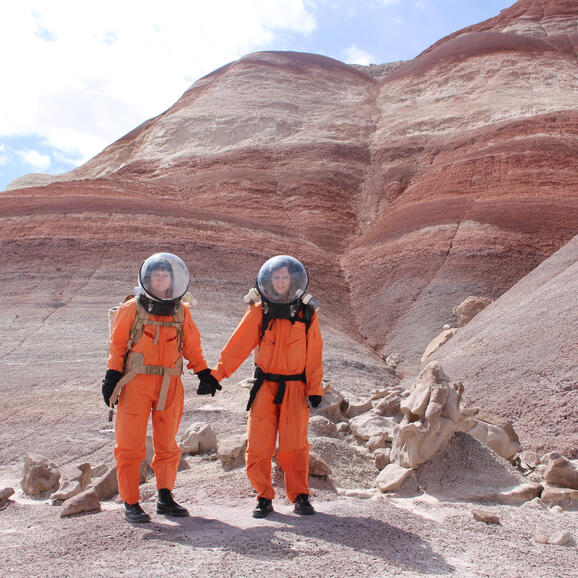 Two women in spacesuits in a barren landscape holding hands