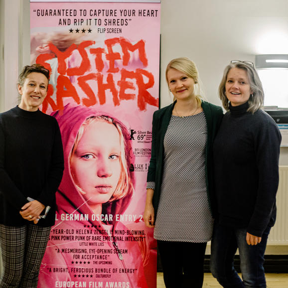 Three women standing with a cinema poster smiling