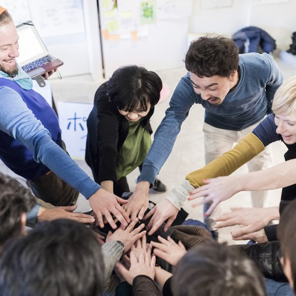Photo of a group of adults with their hands on top of each other in the middle of a circle