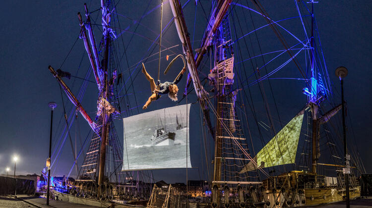 Celluloid Sail - tall ship docked to harbourside with projections on sails and acrobat hanging from rope.