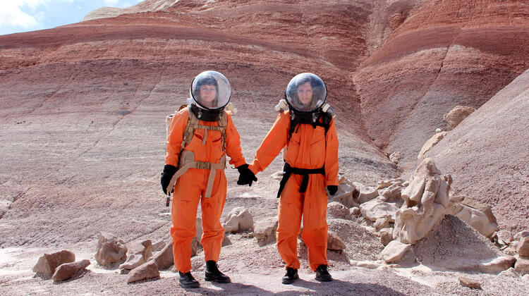 Artists Ella Good and Nikki Kent in orange space suits, from Building a Martian House