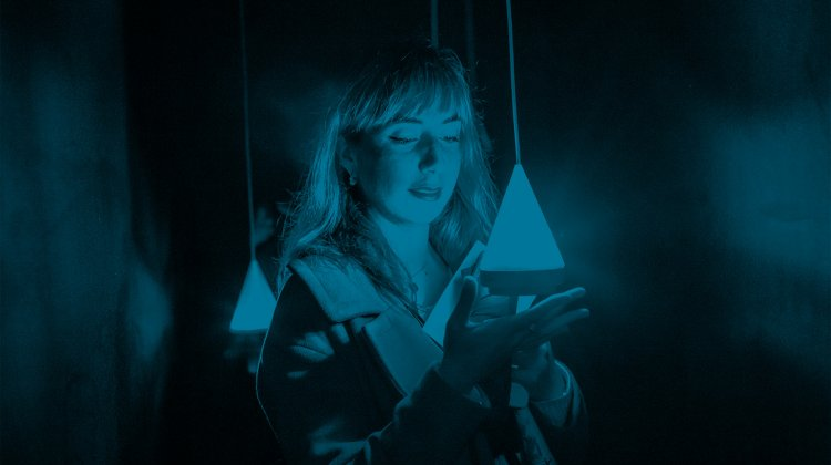 Photo of a woman holding a glowing, suspended digital device