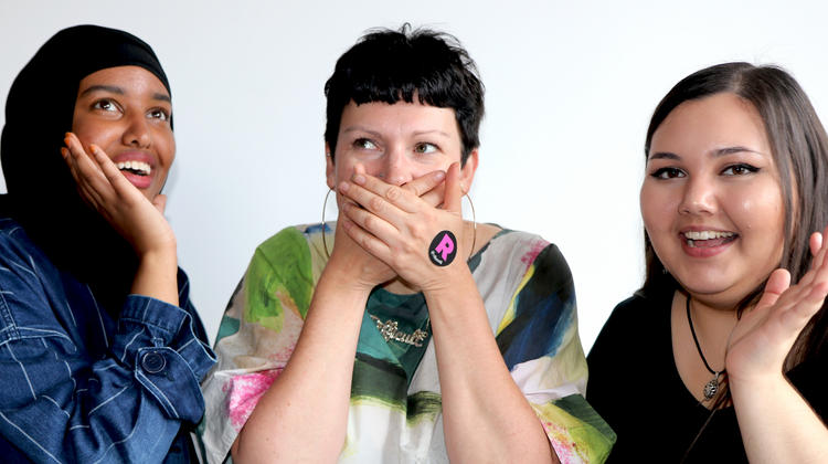 Three women with one covering her mouth with her hands