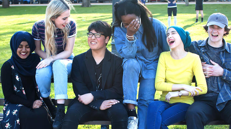 Group of young people on a bench laughing