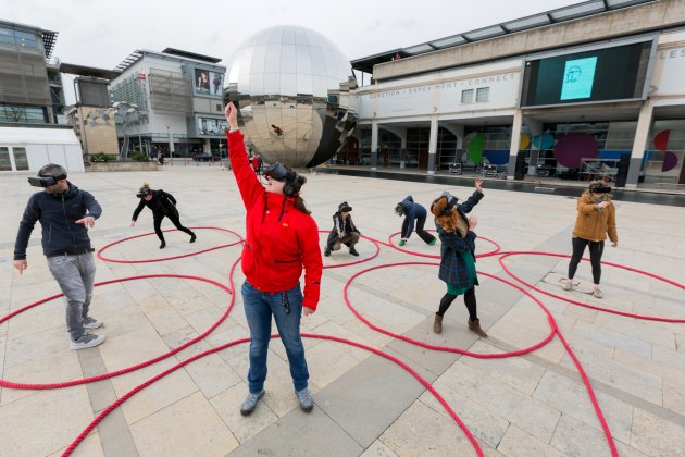 Six people wearing VR headsets and dancing in Millennium Square, Bristol