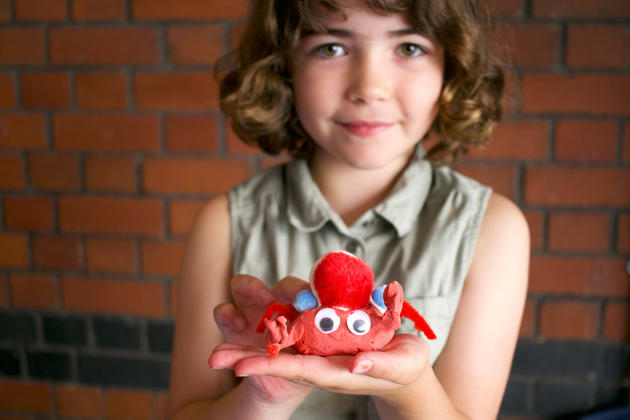 Photo of a child with a clay model made at a Watershed family workshop