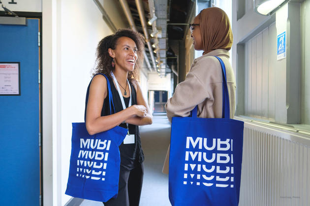 Photo of two people chatting with Mubi branded tote bags
