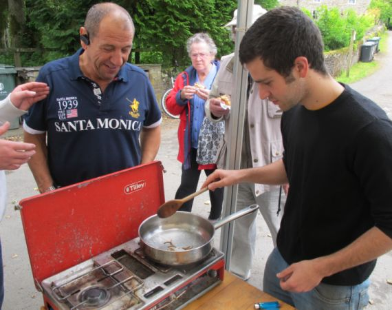 Artist David Lisser cooking insects in his Future food café at Allenheads Village show, 2011