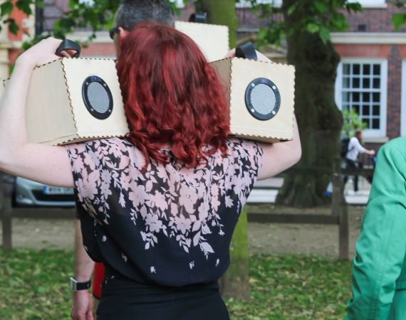 Verity holding two speaker boxes from Duncan Speakman's 'A Folded Path' up to her ears