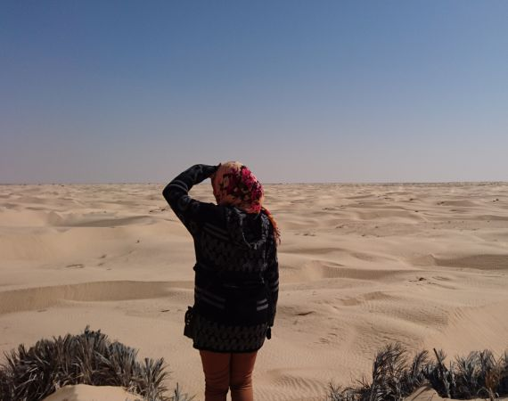 Back of a woman with a headscarf looking in the distance in a desert