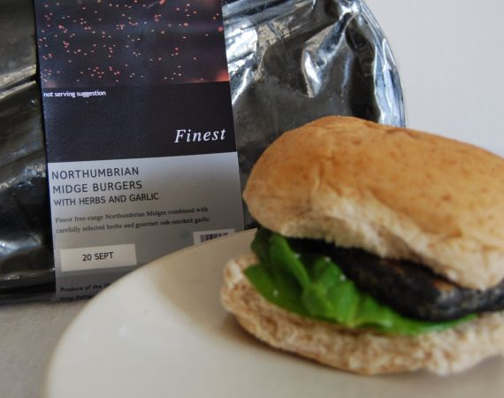 Image of a burger with the supermarket packaging behind it.