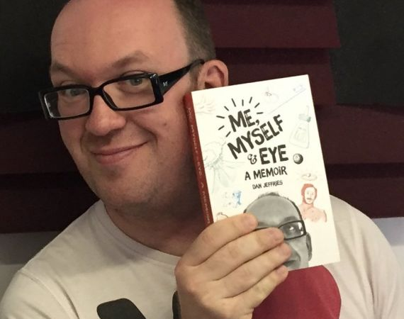 """a white man with glasses holding up a paperback book: """"Me, Myself & Eye: A Memoir"""""""