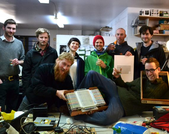 The Canute team posing for the camera with a partially assembled Canute Mk8 and glasses of whisky in a busy workshop.