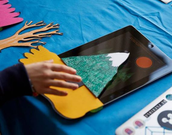 A child's hand using the Bear Abouts paper sensors on an iPad